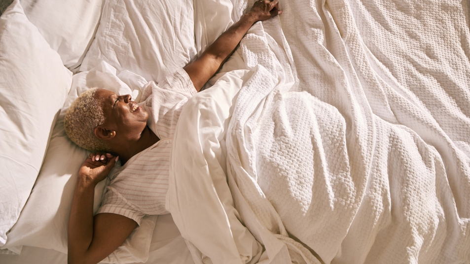 A mature woman wakes up and stretches in early morning light