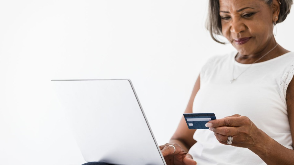 Mature business woman carefully checks numbers on credit card