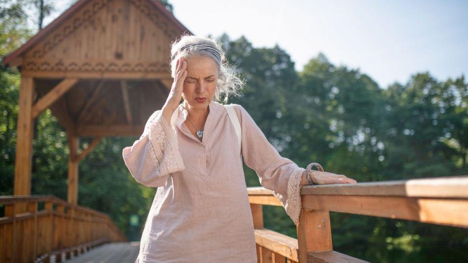 woman having headache pain in the summer