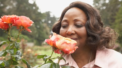 woman smelling roses outside