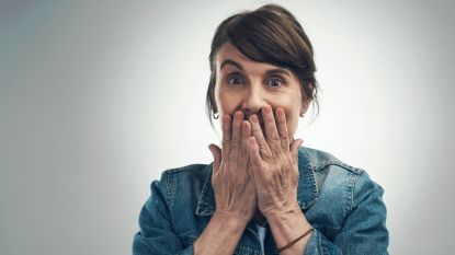 woman covering mouth in embarrassment