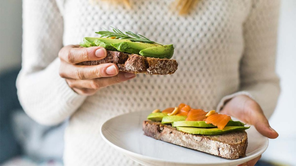 Woman eating avo toast with salmon