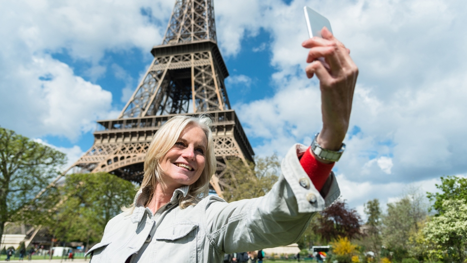 woman taking a selfie in front of the eiffel tower