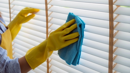 Woman wiping window blinds
