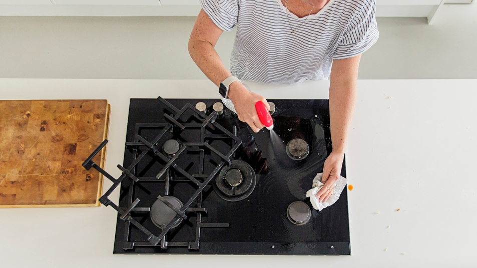Overhead view of a woman cleaning stovetop