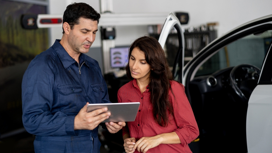 Friendly mechanic showing female customer the work done on her car on tablet at the car workshop both smiling