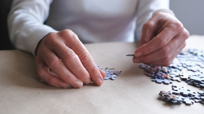 woman putting together jigsaw puzzle
