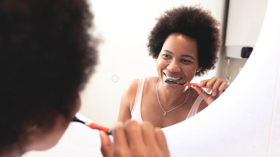 woman brushing her teeth and looking in mirror