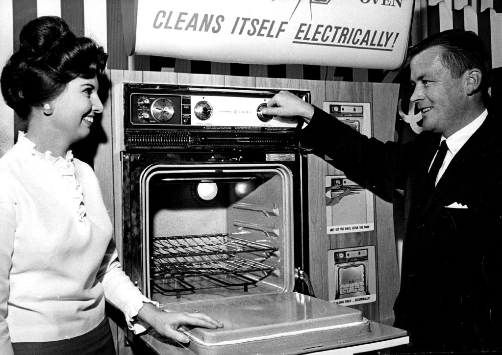 man showing off new oven to woman